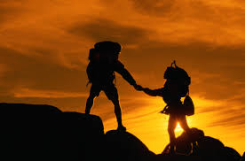 Two Hikers Holding Hands at Sunset